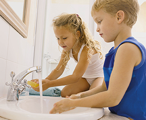 Young girl and boy washing their hands in a bathroom sink