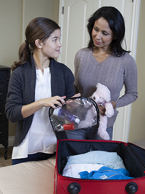Woman and girl packing suitcase.