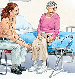 Woman sitting on edge of hospital bed putting on shoe with long-handled grasper. Healthcare provider is sitting next to woman.