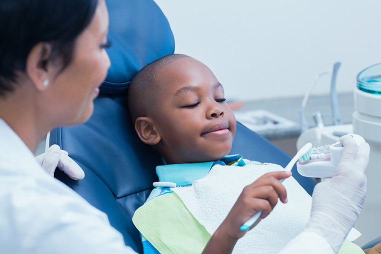Dental healthcare provider showing boy how to brush teeth.