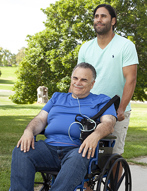 Man with nasal cannula in wheelchair. Another man pushing wheelchair.