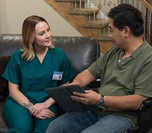 Healthcare provider with digital tablet and man in wheelchair talking in living room.