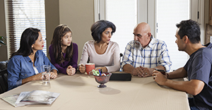 Two men, two women, and teen girl sitting at kitchen table.