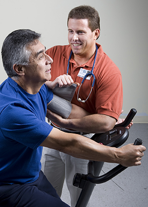 Man exercising on exercise bike while physical therapist takes his blood pressure.