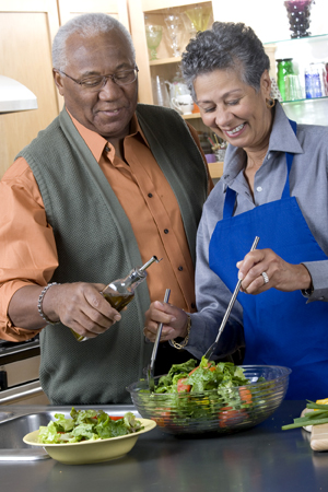 Man and woman fixing a salad together.