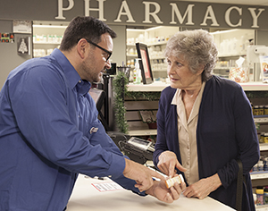 Pharmacist handing woman bottle of pills over counter.
