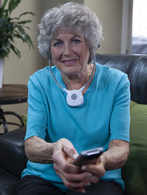 Woman using assistive listening device.