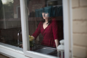 Woman standing in front of a window looking sad.